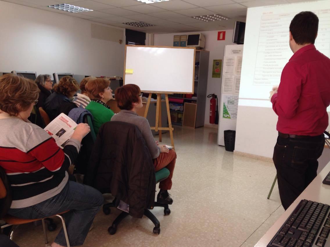Usuaris durant una de les sessions del taller de telèfons intel·ligents, al Punt d'Amposta
