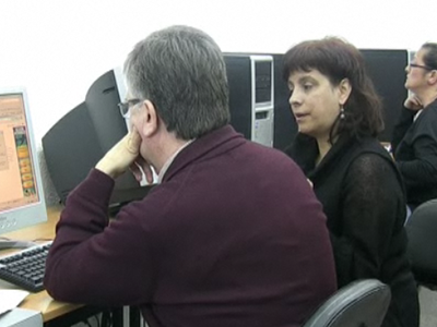 La dinamitzadora i un alumne parlen davant d'un ordinador a l'Òmnia Pomar
