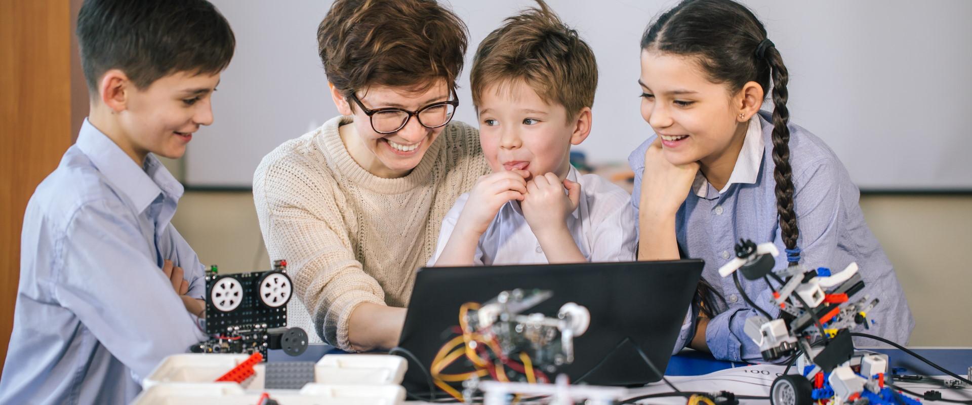Tres infants aprenent tecnologia amb una dona