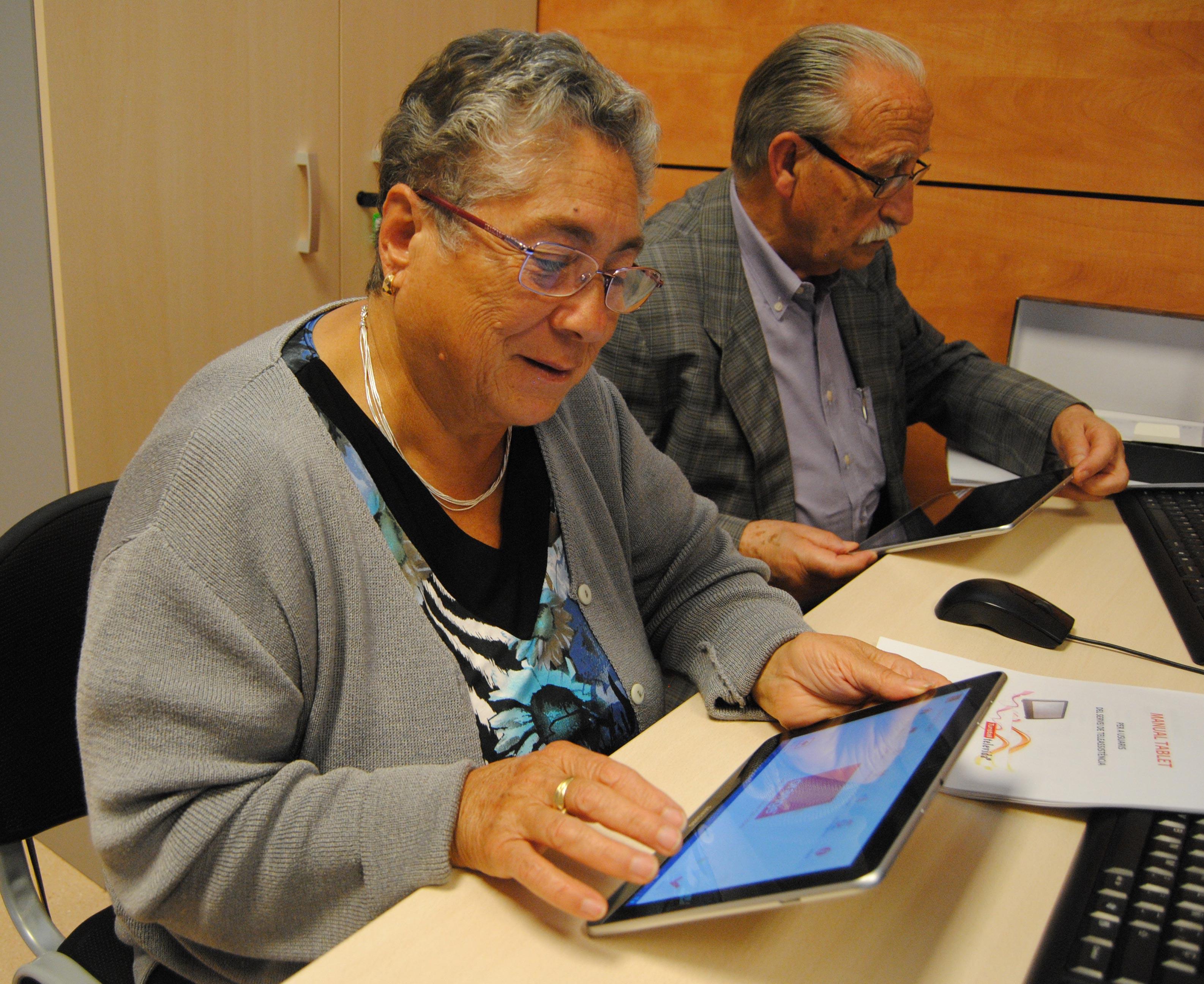 imatge de dos persones grans utilitzant tauletes