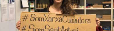 Una dona amb un cartell que diu #SomXarxaCuidadora #SomSantAntoni